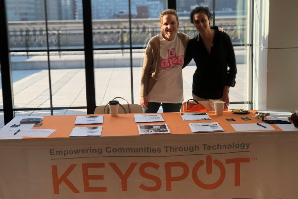 two women standing behind keyspot information table